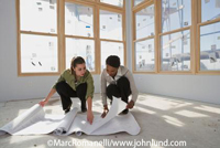 Picture of two women crouched on the floor looking at a set of blueprints in a new home under construction